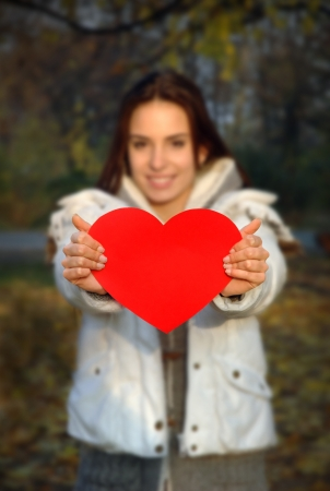 woman out of focus holding paper in shape of heart  Focus is on the heart which is flat, convenient for text