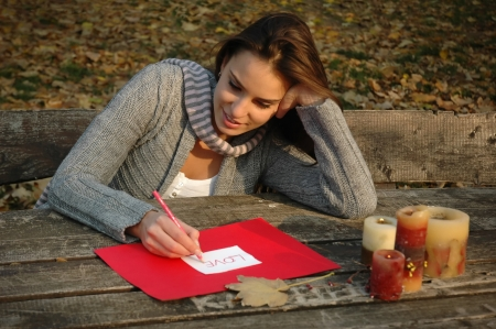 young female  writing word love on white and red paper, on a old wooden table with candles and autumn leaf on it  Sitting on old  raw  bench, leaning head on arm Stock Photo