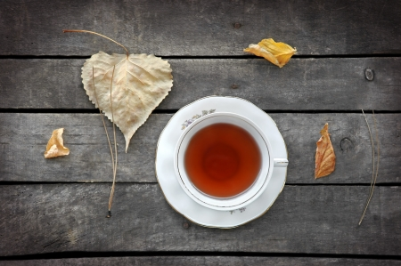 autumn tea in white vintage cup on old grey rustic wooden table, with autumn leaves and pine needles Stock Photo