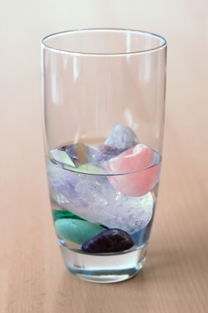 light transmission: different kinds of gemstones in glass of water, on wooden table, making elixir  Stock Photo