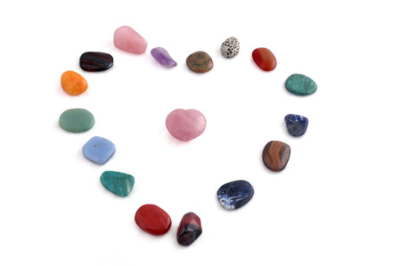 Small processed, polished,  crystals arranged in shape of heart, various kinds, on white background