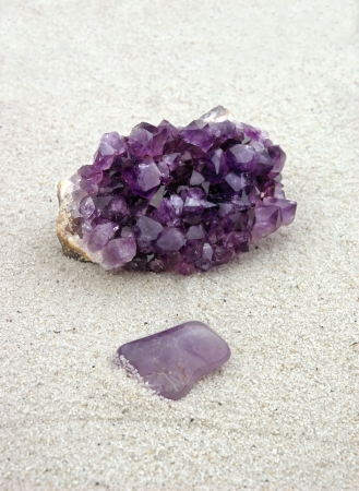 Amethyst, rough and smooth, processed and unprocessed, polished and raw, purple crystals on sand