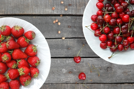 top view of horizontal diagonal composition of strawberries and sweet cherries on white plates, on old gray wood table Imagens