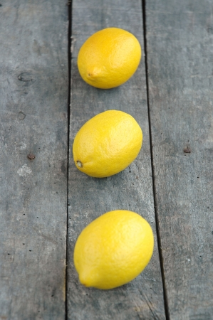 Vertical composition of three lemons on grey wood background