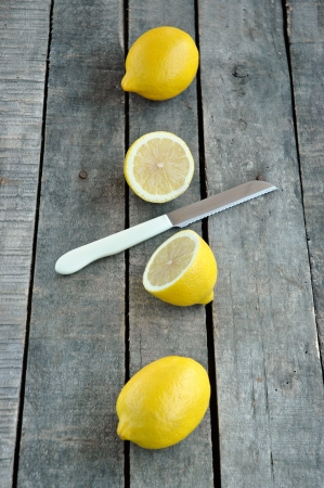 vertical composition of whole and cut lemon with knife on gray wood background