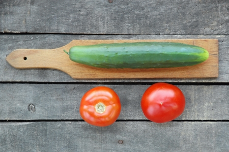 one cucumber on cutting board with two tomatoes on gray wooden background Stock Photo
