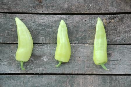 Three green peppers on gray wooden background Stock Photo