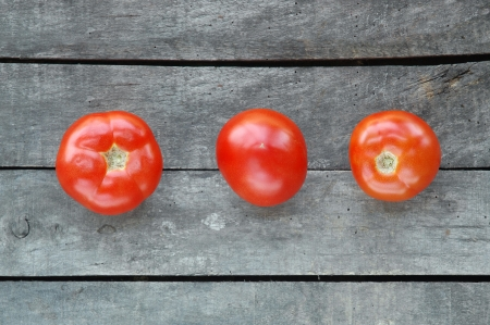 Three tomatoes on gray wooden background