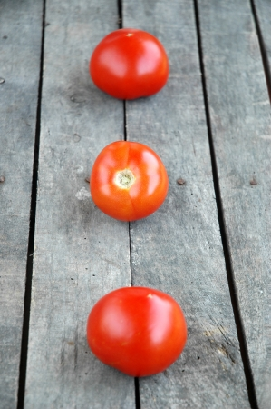 Three whole tomatoes on wooden background  Vertical composition