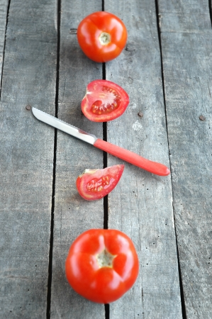 Whole and cut tomatoes on gray wooden background