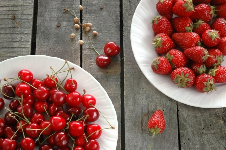 horizontal composition of strawberries and cherries on white plates, on old table, in perspective