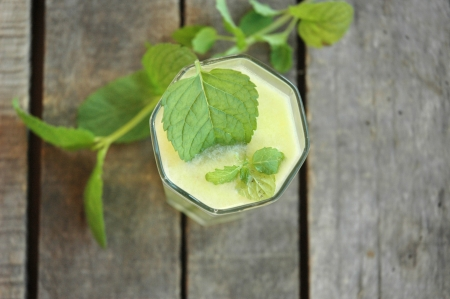 top close-up of glass of lemonade with mint leafs in glass, and mint twig on table