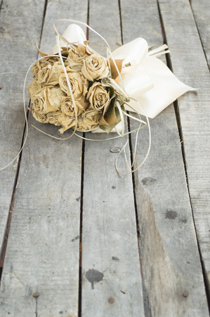 Dried yellow roses on old table with copy space