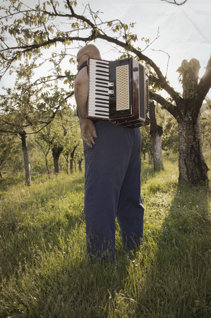 Old man with accordion on his back in field photo
