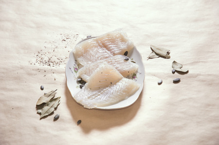 pangasius: Horizontal image of raw pangasius fish with spices on plate, copy space Stock Photo