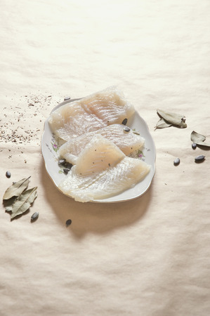pangasius: Vertical image of raw pangasius fish with spices on plate, copy space