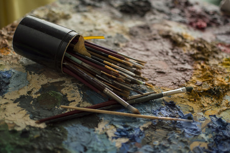 laying down: Brushes for painting in black jar, laying down on palette of dry mixed oil colors