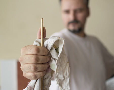 proportions of man: Close up of painters hand measuring proportions with the handle of the brush, thumb method