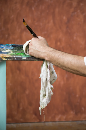 spontaneous painting: Detail of painters hand with brush and rag leaned on palette