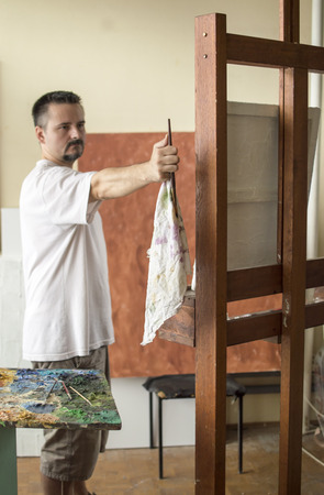 proportions of man: Painter measuring proportions with brush and rag in hand with  thumb method, hand and brush are in center of image Stock Photo