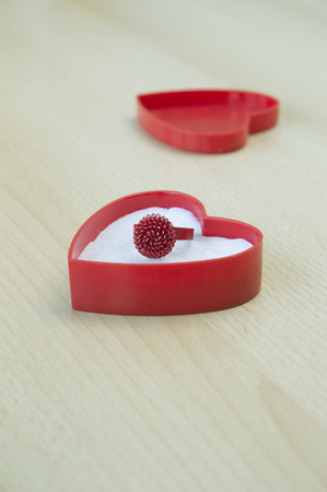 Old red ring in gift box on wooden table photo