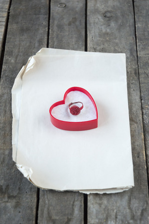 Ring in opened gift box in shape of heart  on paper and gray wooden background