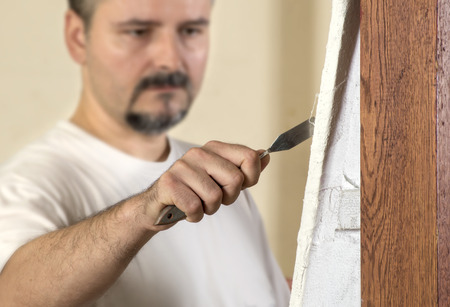 trowel: Painter working with trowel on canvas, focus on trowel