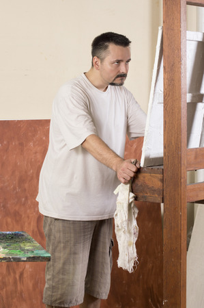 observe: Vertical image of painter while observe a detail on canvas