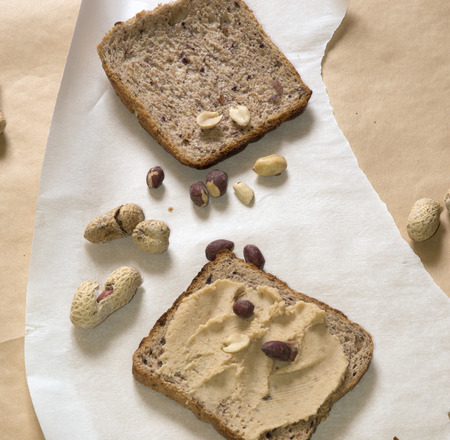 pumpernickel: pumpernickel bread with peanut butter and peanuts, peeled and unpeeled, in shell Stock Photo