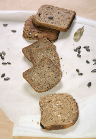 unleavened: Different kinds of unleavened and pumpernickel bread, with pumpkin seeds and bay leaf, on white and brown paper, vertical composition Stock Photo