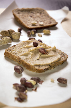 pumpernickel bread with peanut butter and peanuts, peeled and unpeeled, in shell Imagens