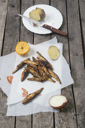 Fried smelt with lemon and onion on white baking paper, and potato on white plate Imagens