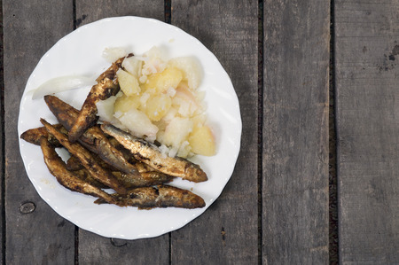 Fried smelts with potato salad on white plate, gray wood background, copy space