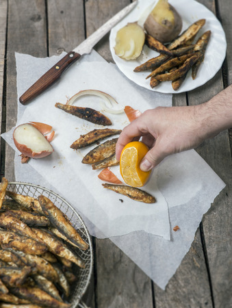 Male hand squeezing lemon as spice on fried smelt fish