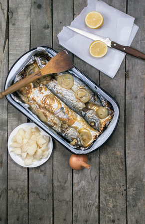 Top view of baked mackerel fish in casserole with wooden scoop on old wooden table with whole onion,  lemon and potato salad on gray wooden background. Copy space at the bottom of image.