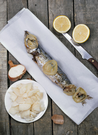 Vertical image of baked mackerel on white paper with potato salad, lemon and onion; on gray wooden background. Top view.