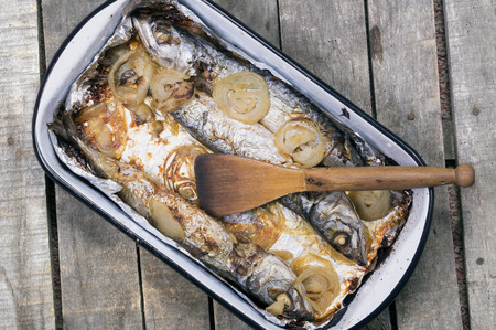 baked mackerel fish in casserole with wooden scoop on wooden background