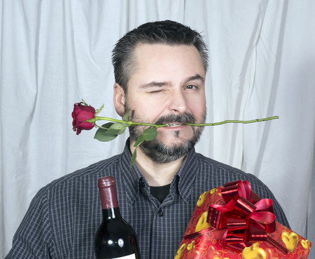 Male winking holding rose in mouth, bottle of wine and present