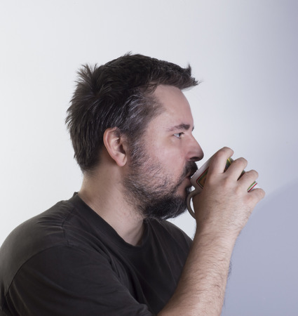 man with beard drinking something from the cup