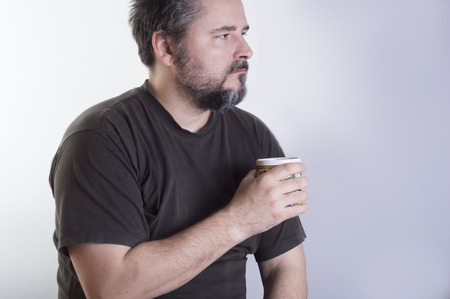Man with beard holding a cup
