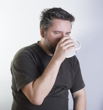 wakening: hipped man with beard drinking morning coffee