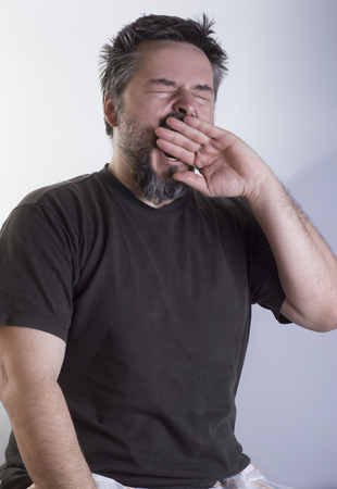 Vertical image of sleepy man with beard, yawn