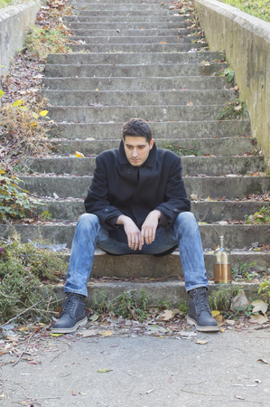 Depressed young man sitting on concrete stairways with bottle of alcohol drink beside him