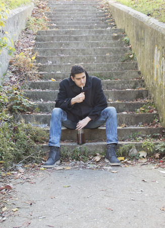 Young man smoking and drinking on outdoor stairways