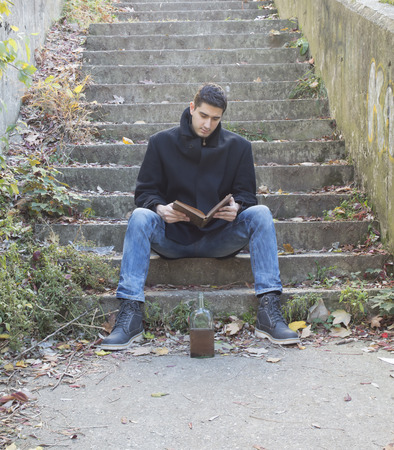 young man reading on stairways with bottle of alcohol