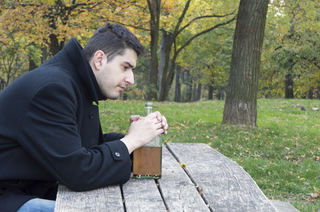 depressed man in nature holding  bottle of alcohol drink  thinking