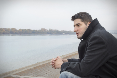 Young man sitting at the riverside and thinking Stock Photo
