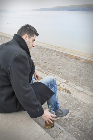 Depressed man with bottle of alcohol drink sitting at the riverside