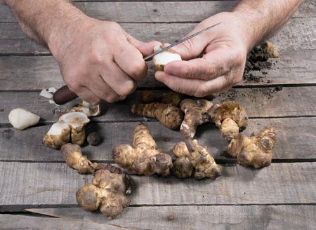 Man peel raw Jerusalem artichoke on wooden background