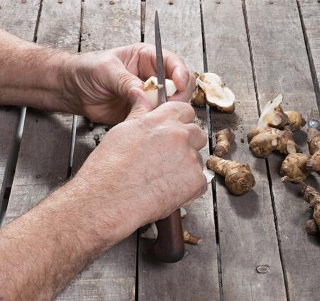 Man preparing artichoke, cutting, peel, for cooking